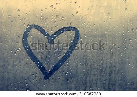 Autumn rain, the inscription on the sweaty glass - love and heart - stock photo