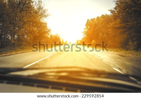 Autumn road at sunset with rays of light - stock photo