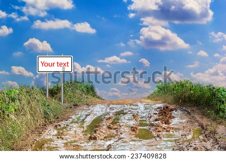 Autumn rural landscape with the dirty road and traffic sign. - stock photo