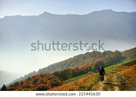 Autumn scene with a motorcycle on a mountain dirt road at golden hour  - stock photo