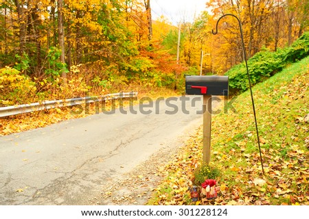 Autumn scene with road and mailbox - stock photo