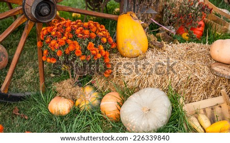 Autumn scene: wooden wheel, pumpkins and a bale of hay - stock photo