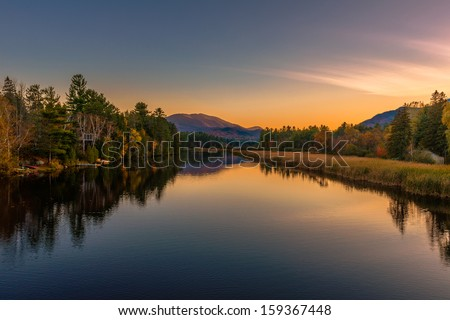 Autumn scenery at sunset reflected in the water of the river - stock photo