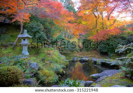 Autumn scenery of a Japanese garden in Kyoto, Japan ~ A stone lantern by the pond with fiery maple foliage reflecting on the water - stock photo
