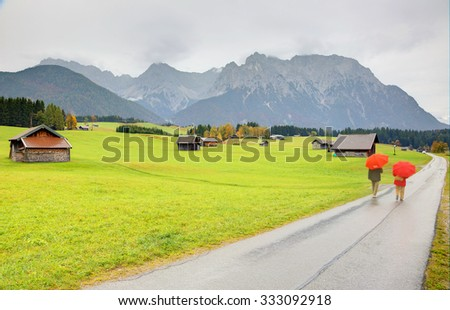 Autumn scenery of a ranch farmland in a foggy morning near Mittenwald ~ a road passing through a meadow dotted with wooden barns with Karwendel Mountains in the background, in Bavaria, Germany - stock photo