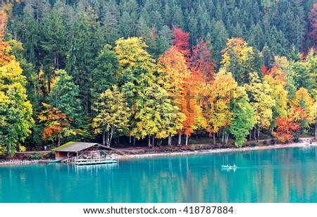 Autumn scenery of Alpsee with view of tourists rowing a boat toward a boathouse by lakeside & colorful fall foliage reflecting on emerald lake water in Hohenschwangau near Fussen in Bavaria, Germany - stock photo