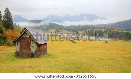 Autumn scenery of Lake Geroldsee in a foggy morning, an alpine lake between Garmisch-Partenkirchen and Mittenwald with Karwendel Mountains in the background, Gerold, Bavaria, Germany - stock photo