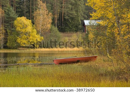 autumn scenery with lake, cabin and boat - stock photo