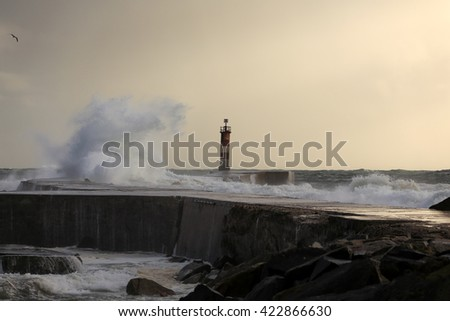Autumn seascape with interesting light filtered by moisture seeing stormy waves - stock photo