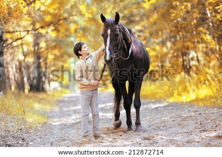 Autumn season happy teenager boy and horse walking in forest - stock photo