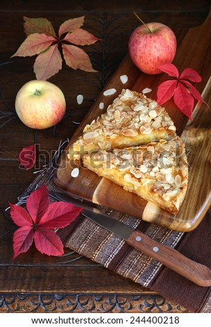 Autumn still life: apple tart, colorful leaves on an old wooden table - stock photo