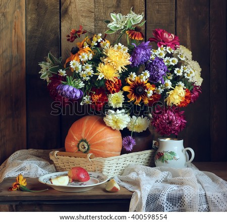 Autumn still life in rustic style pumpkin, a bouquet of flowers and pieces of Apple on the old plate on the background of boards. - stock photo
