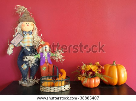 Autumn still life of scarecrows, pumpkins and flowers sitting on a black bench with a red textured background with copy space. - stock photo