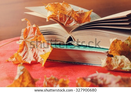 Autumn still life -  stack of old books among the dry yellow maple leaves and bright sunlight.  Selective focus at the book's spine - shallow depth of field - stock photo