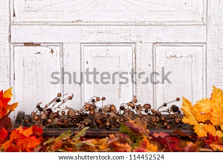 Autumn still life with acorns and leaves with wooden panel for background - stock photo