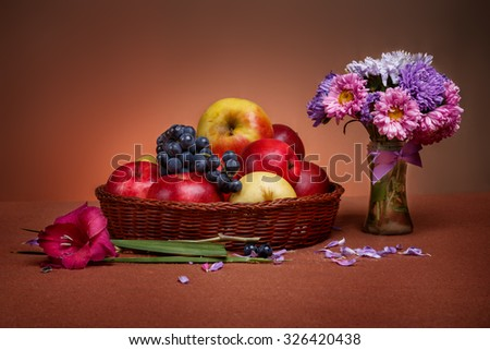 Autumn still life with apples, grape and bouquet of flowers in glass vase - stock photo