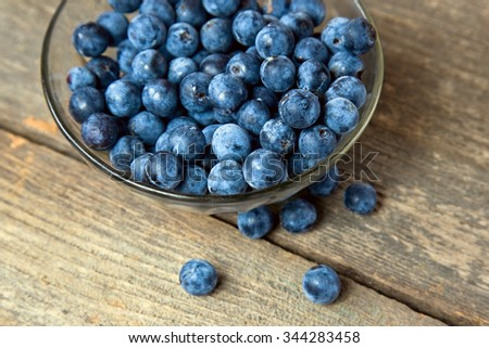 Autumn still life with blackthorn branches fresh juicy ripe berries in a bowl on a wooden table. (Prunus spinosa or sloe) - stock photo