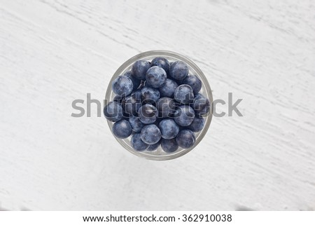 Autumn still life with blackthorn branches fresh juicy ripe berries in a bowl on a wooden white table. (Prunus spinosa or sloe) - stock photo