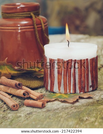 autumn still life with cinnamon candle and barrel of honey on old wooden table to decorate Thanksgiving card  - stock photo