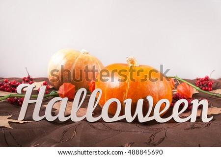 Autumn still life with copy space. Pumpkin with flowers, maple leaves and Halloween holiday text