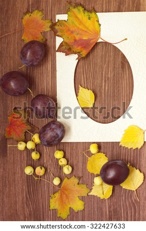 Autumn still-life with little yellow apples, plums, photo frame, colorful leaves, wooden background