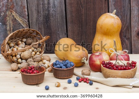 Autumn still life with pumpkins and autumn berry and vegetables on old wooden background, closeup, selective focus - stock photo