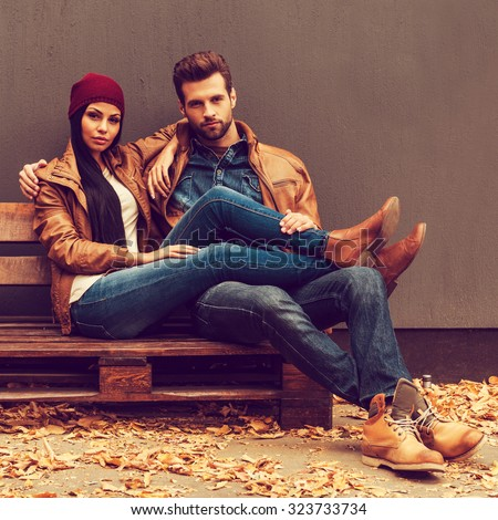 Autumn style. Beautiful young couple bonding to each other while sitting on the wooden pallet with grey wall in the background and fallen leaves laying on the floor - stock photo