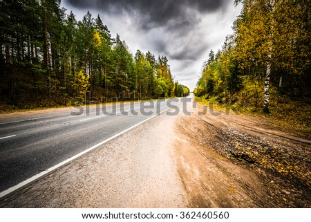 Autumn suburban highway. The view from the side of the road, image vignetting and hard tones - stock photo