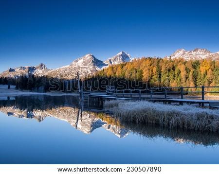 Autumn sunrise mirror reflection in lake Lej da Staz, Engadine, Saint Moritz, Switzerland. - stock photo
