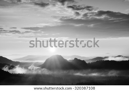 Autumn sunrise panorama  in a beautiful mountain within inversion. Peaks of hills increased from foggy background.Black and white photo