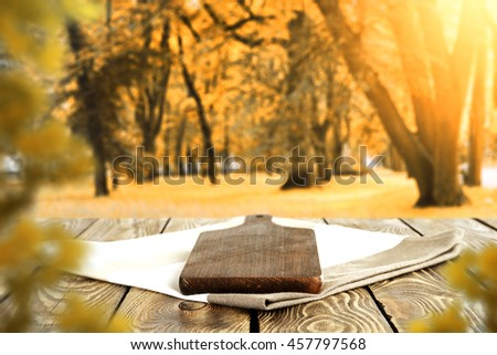 autumn sunset time in park with old trees and dark wooden old table place