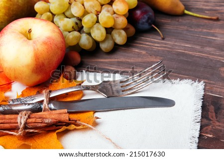 Autumn table setting with apples, plums, grapes and yellow leaves - stock photo