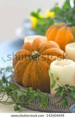 Autumn table setting with candles and pumpkins - stock photo