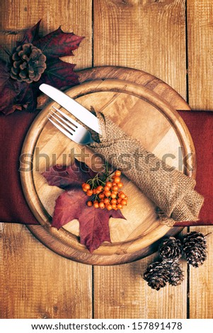 Autumn table setting with knife and fork wrapped in rustic burlap - stock photo