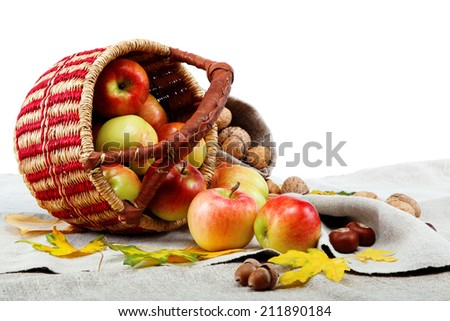 Autumn theme. Apples in a basket and walnuts on linen canvas. - stock photo