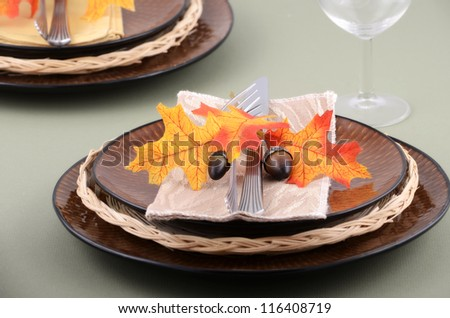 Autumn theme place setting with brown plates and colorful fabric leaves on pale green background