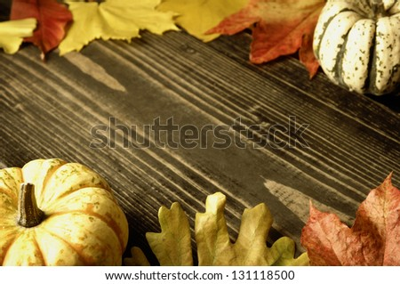 Autumn theme; pumpkins, leaves and hazelnuts on rustic surface with copyspace