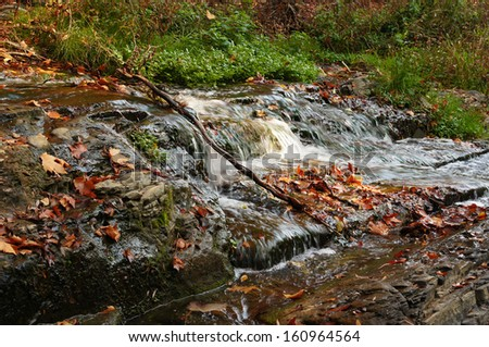 Autumn time: Large rain forest waterfall, sun beams, and mossy rocks - stock photo