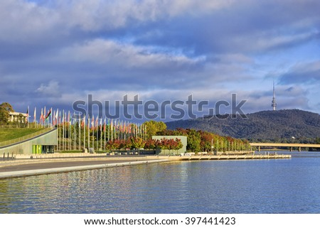 autumn trees on a wateredge of Lake Burley Griffin in Canberra under warm morning sun with Flags in background.