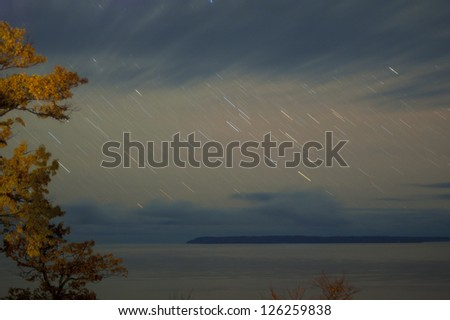 Autumn trees with storm clouds and star trails in sky- over lake with island in distance - stock photo