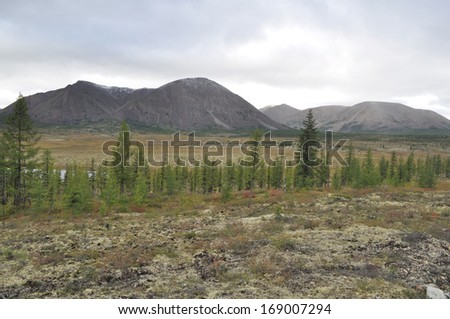 "Autumn tundra on the background of mountains in Yakutia. Cloudy landscape in the route area ""Kolyma"", Yakutsk - Magadan. Russia."