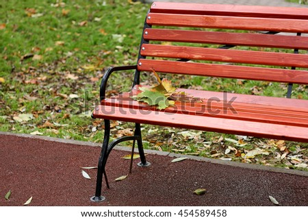 Autumn urban landscape. Part of the wooden benches in the Park, on which lay a small bouquet of autumn maple leaves. - stock photo