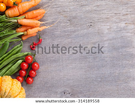Autumn vegetables background: tomatoes, carrots, pumpkin, runner beans, chilies - stock photo