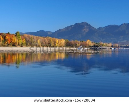 Autumn view of hills of Low Tatras mirrored in deep waters of Liptovska Mara lake, Liptov region, Slovak republic. Colorful trees on shore of Liptovska Mara can be seen in foreground. - stock photo