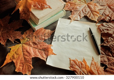 Autumn vintage still life - stack of old books with yellowed sheet of paper and old vintage ink pen on the table among yellow maple leaves.  Selective focus at the ink pen - shallow depth of field - stock photo