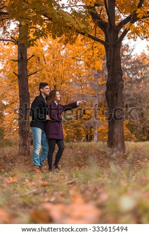 Autumn walk. Young happy couple on a walk in the park - stock photo