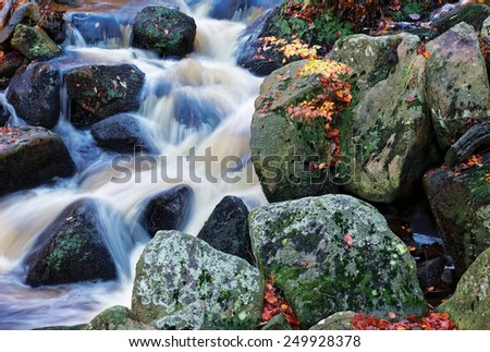 Autumn waterfall closeup with rocks and red and yellow leaves - nature background - stock photo