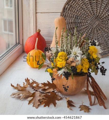 Autumn window design with a pumpkin, seeds and flowers of chrysanthemums