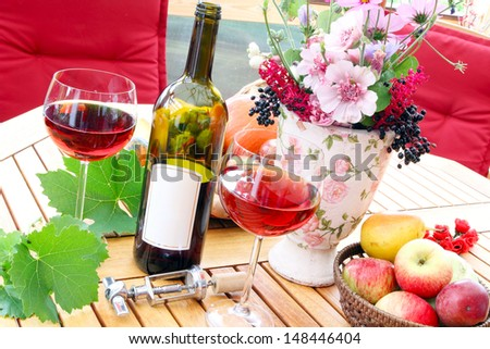 Autumn with red wine on the terrace - stock photo
