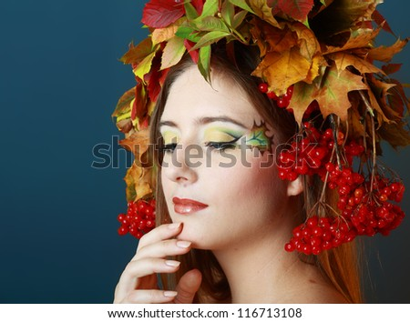 Autumn Woman. Beautiful makeup face art close up and hat from autumn yellow and red leaves - stock photo